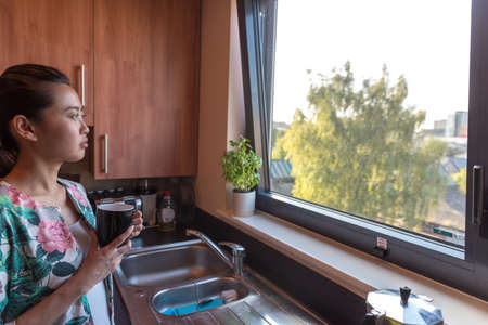 view to outside: Smart Asian Business Woman Having A Coffee in the Morning in her Kitchen Before She Goes to Work.