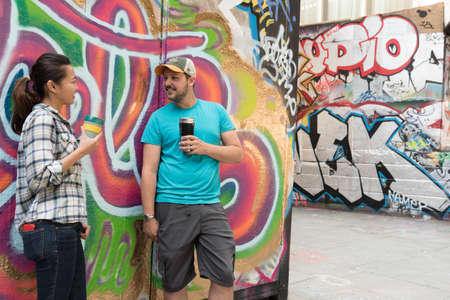 adult student: Young Couple Drinking Coffee and Chatting in Concrete Urban Skate park with Very Colorful and Vibrant Graffiti