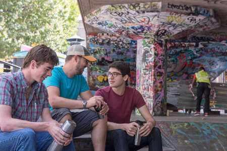 copy sapce: Three Casual Young Adults Drinking Coffee and Chatting in Graffiti Skate Park