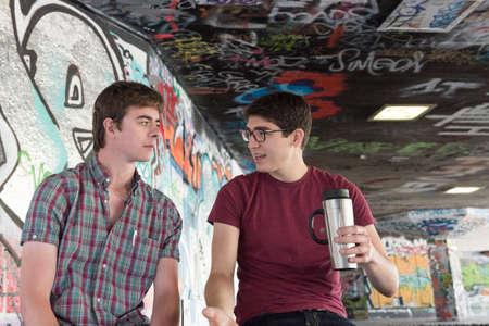 skate park: Three Casual Young Adults Drinking Coffee and Chatting in Graffiti Skate Park