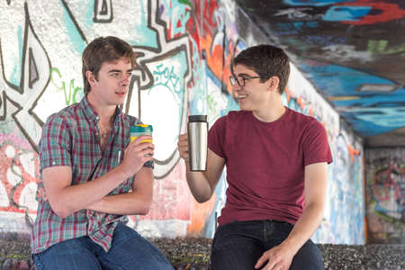 copy sapce: Two Casual Young Adults Drinking Coffee and Chatting in Graffiti Skate Park Editorial