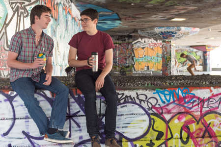 skate park: Two Casual Young Adults Drinking Coffee and Chatting in Graffiti Skate Park Editorial