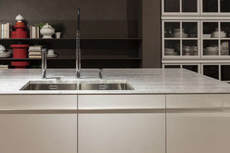背景の白大理石カウンターと食器棚でキッチンをきれい。 写真素材