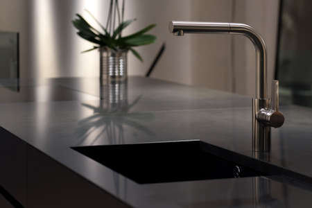 stone worktop: Dark Solid Granite Sink with Modern Stainless Steel Faucet Tap Stock Photo