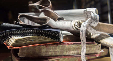 made to measure: Collection of Tailors Scissors, Suit Cloth, Tape Measure and Books Together.
