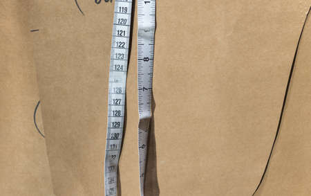 tailors tape: Tailors Tape Measure with Plain Brown Paper Pattern Backgroun