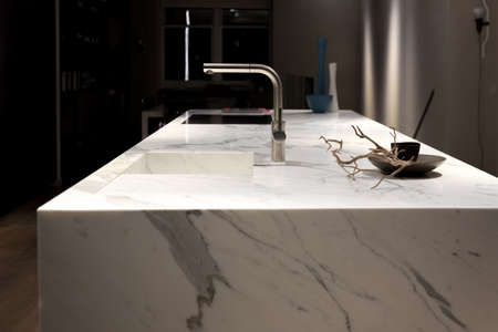 Stylish Solid White Marble Kitchen Counter With Dark Cupboards Archivio Fotografico
