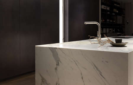 classy house: Stylish Solid White Marble Kitchen Counter With Dark Cupboards Stock Photo