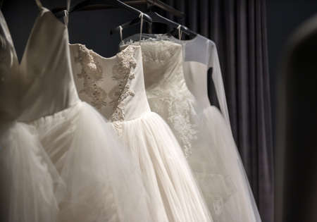 Selection of handmade white wedding gowns hanging on a rail in a darkened room partially illuminated by a light 版權商用圖片