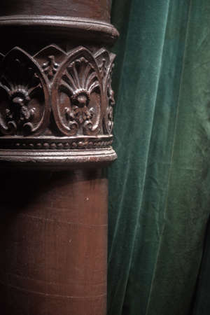 Ornate acanthus decoration on a brown painted cast iron pole in a room interior in front of a green drape or curtain 版權商用圖片