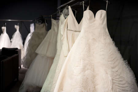 Selection of white wedding dresses or ball gowns on display hanging on rails with selective focus to one illuminated by a highlight