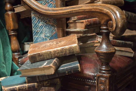 Vintage baroque armchair with old books against green curtain Banque d'images