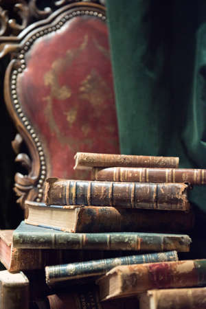Vintage baroque armchair with old books against green curtain 版權商用圖片