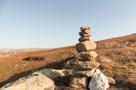 Tall stack of natural irregular stones balanced on top of one another in open grassland in a country landscape conceptual of the art of stone stacking, a memorial or route marker