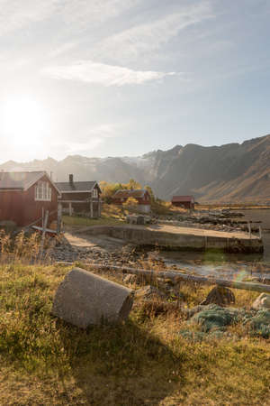 Beams of light with lens flare over a mountain peak shining down over a hut on the shoreline in Tromso, Norway on a misty day in a scenic rural landscape 版權商用圖片