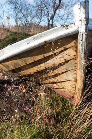 Old wooden dinghy rowboat beached on grass viewed close up on the prow with detail of the hull against a blue sky 版權商用圖片