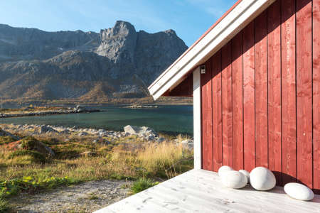 Close up cropped view of a wooden Norwegian beach hut with stones on the shoreline overlooking the Tromso Fjord, Arctic Circle, Norway and mountain peak on a sunny blue sky day