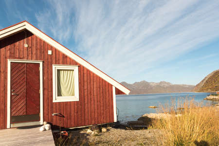 View of a wooden Norwegian beach hut with stones on the shoreline overlooking the Tromso Fjord, Arctic Circle, Norway and mountain peak on a sunny blue sky day 版權商用圖片