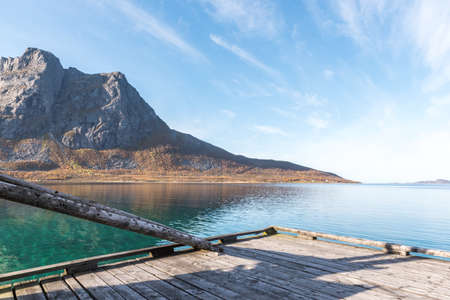 Wooden Boardwalk Jetty Pier with Still Ocean Water with Mountains in Background 版權商用圖片