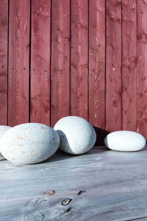 Smooth Round Stones on Wooden Decking against Cladding