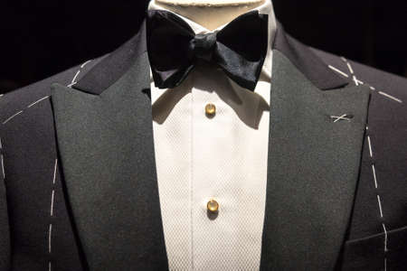 Close up on top part of tailored jacket on mannikin with black bow tie and sequined buttons on shirt 版權商用圖片