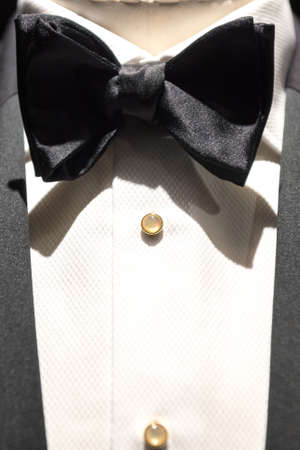Close up on top part of tailored jacket on mannikin with black bow tie and sequined buttons on shirt Фото со стока