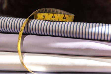 Maßband und Stoffmuster des Schneiders. Gefaltetes Herren Hemdentuch Standard-Bild