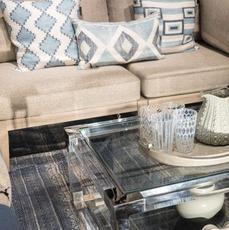 Glass Coffee Table next to Sofa with patterned glasses and textured jug