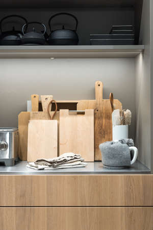 Collection of Chopping Boards on Metal Kitchen Counter with Teapot and Toaster 版權商用圖片