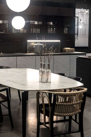 Dark Tone Kitchen with White Marble Table and Low Key Furniture and Cabinets.