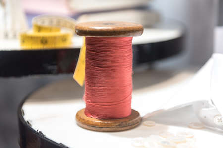 Tailor's Table with Red Thread and Tape Measure and Shirt Cloth Swatches 版權商用圖片 - 131750810