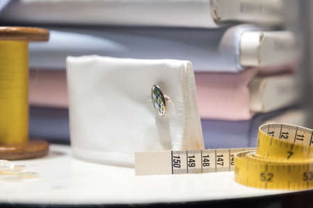 Tailor's Table with Thread and Tape Measure and Shirt Cloth Swatches