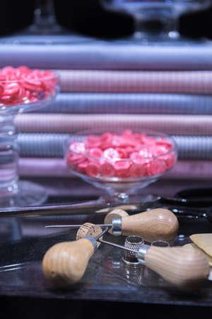 Schneiderschere, Ahle, Kreide und Fingerhut präsentiert auf Glastisch, umgeben von Knöpfen und Hemdenstoff