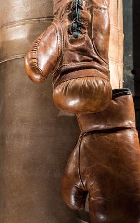 Worn Brown Leather Boxing Gloves Hanging next to Punch Bag 版權商用圖片