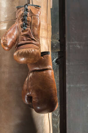 Classic Brown Boxing Gloves with Punch Bag and Wooden Background 版權商用圖片 - 143076682