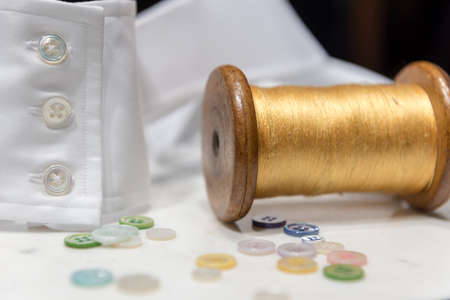 Wooden Spool with Yellow Threas with Assorted Buttons and White Shirt Cuff 版權商用圖片 - 143076714