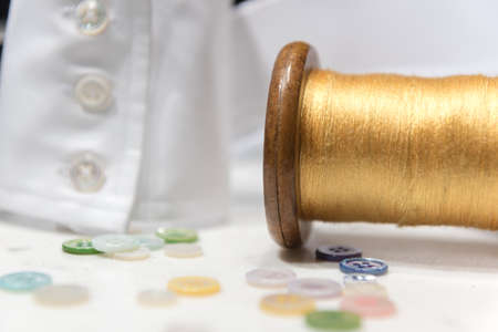 Wooden Spool with Yellow Threas with Assorted Buttons and White Shirt Cuff