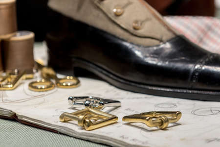 Cobblers' Table With Gold Buckles, Various Accessories, Leather Shoes and Sketch Drawings