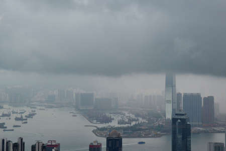 High modern buildings and boats in fog and thick rain clouds of Hong Kong harbor from view point 版權商用圖片