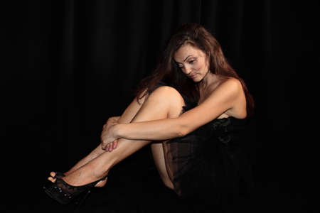 girl in a black dress on a black background Stock Photo