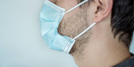 A man putting on disposable surgical mask to prevent spreading of the viruses or contagion