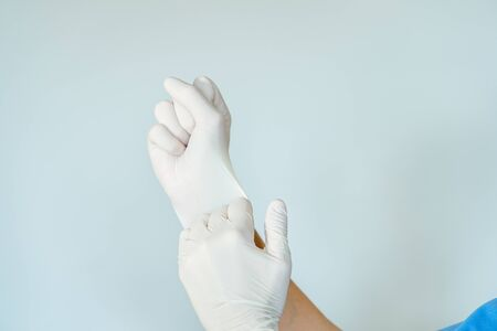 Healthcare professional putting on surgical latex gloves