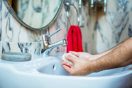 Man washing her hands with soap in a hygienic way in her home sink. bathroom Stok Fotoğraf
