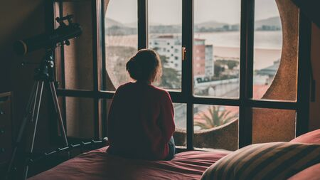 Girl looking through the window of her room sitting on the bed. In the background is the beach. Feeling of sadness, longing