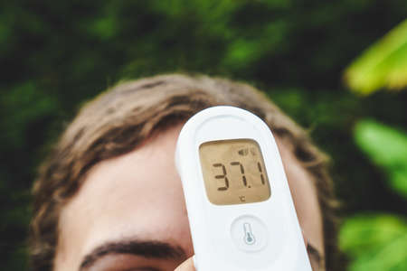 Infrared digital forehead thermometer measuring the fever or body temperature of a girl during the covid-19 pandemic. The person tests positive for a fever. It measures in degrees centigrade. Stok Fotoğraf