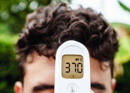 Infrared digital forehead thermometer measuring the fever or body temperature of a boy during the covid-19 pandemic. The person tests positive for a fever. It measures in degrees centigrade.