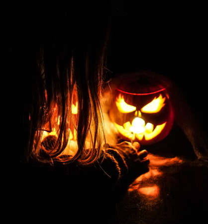 A girl prepares and decorates her pumpkins for Halloween, with terrifying faces, cobwebs and illuminated spiders inside. Candlelight at night or dark. Stok Fotoğraf
