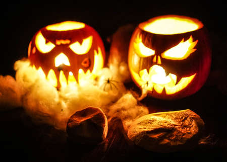 Two pumpkins carved prepared for Halloween, with terrifying faces, cobwebs and illuminated spiders inside. Light with candles.