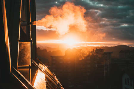 Beatiful smoke vent, on the roof of a flat because of the gas heating on a cold day with a spectacular sunset. Natural vent expel smoke outside using the exhaust pipe.