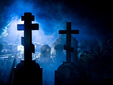 Crosses and tombstones silhouettes in the blue foggy night 写真素材